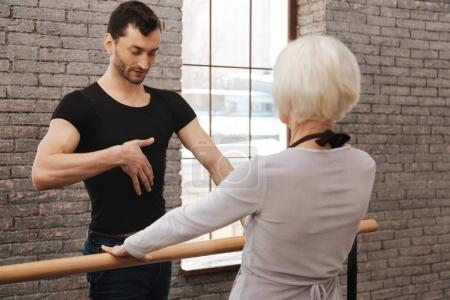 Confident dance teacher instructing elderly woman in the dance studio