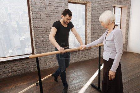 Mature dance teacher instructing aged woman in the ballroom