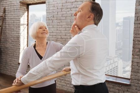 Optimistic aged dance couple rehearsing in the dance studio