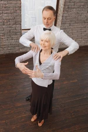 Supportive retired couple performing in the dance studio