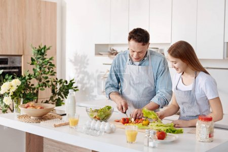 POsitive father and his daughter cooking together