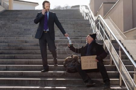Successful businessman giving money to poor man