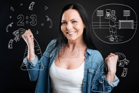 Delighted cheerful woman holding bags with money
