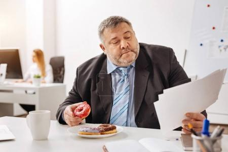 Busy engaged employee eating at his workplace