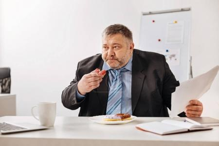 Stressed employee stuffing himself with baked sweets