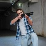 Постер, плакат: Confident skilled shooter sitting on one knee