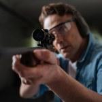 Постер, плакат: Handsome professional sniper looking into the optical sight