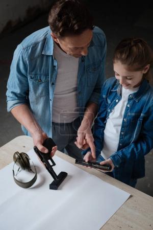 Nice pleasant man showing his daughter a gun
