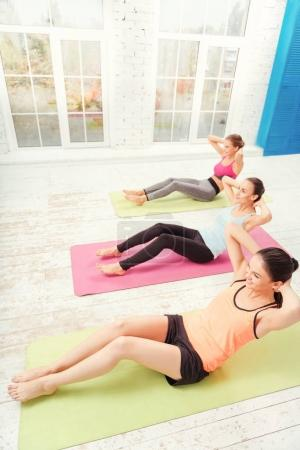 Top view of women doing abdominal crunches at gym