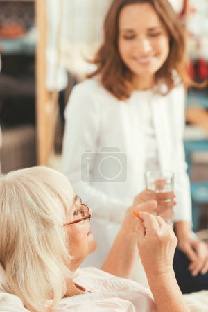 Careful old woman taking medicament at home