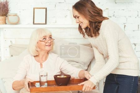 Positive young granddaughter taking care of pensioner at home