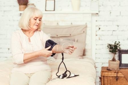 Skillful elderly lady measuring blood pressure at home