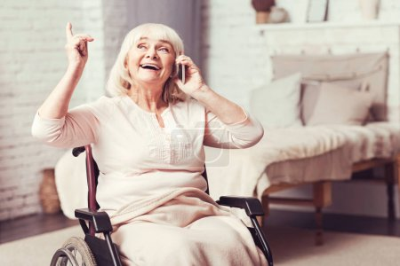 Joyful disabled old woman talking on phone at home