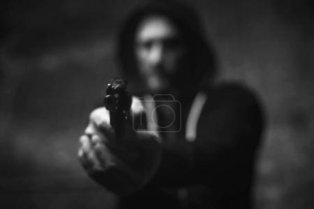 Dreaded brutal bandit holding his victim on gunpoint
