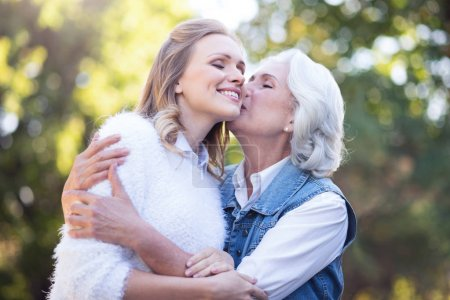Aged mother kissing daughter in park