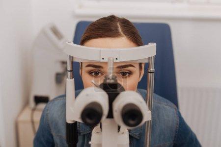 Pleasant attractive woman looking into binoculars
