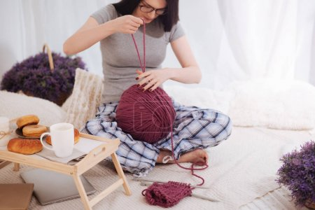 Inventive woman using ball of wool at home