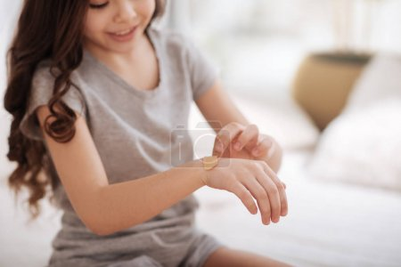 Concentrated girl putting aid plaster on her cut at home