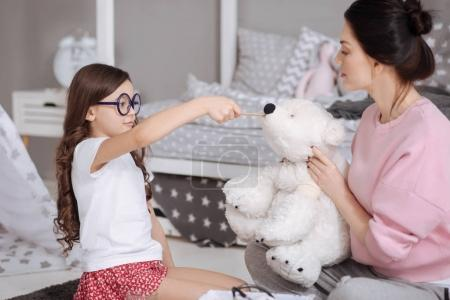 Caring little kid enjoying treating toys with mother at home