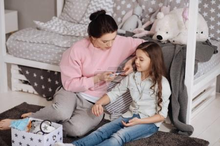Peaceful mother treating daughter at home