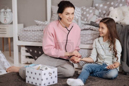 Charismatic young mother having fun with daughter at home