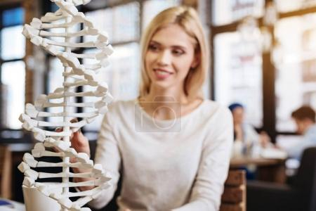 Smiling beautiful young student studying DNA model