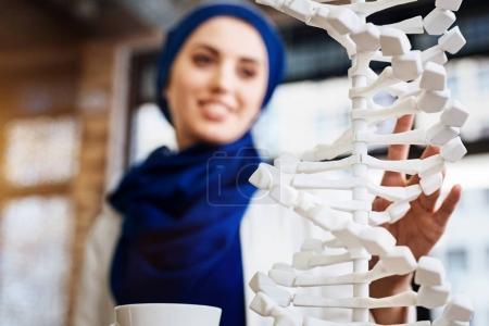 Selective focus of DNA model in hands of muslim student