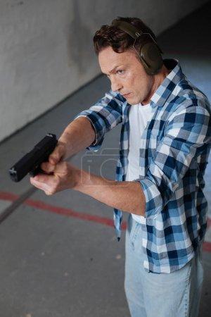 Handsome good looking man directing his handgun