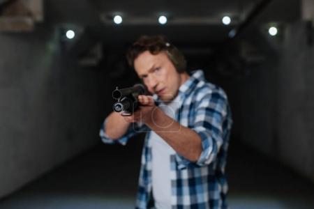 Photo pour Visant la cible. Beau tireur d'élite habile tenant le fusil et choisissant la cible tout en se préparant à tirer - image libre de droit