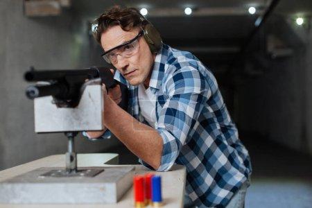 Photo pour Des lunettes de protection. Homme sérieux brutal confiant portant des lunettes de sécurité et visant la cible tout en utilisant le fusil - image libre de droit