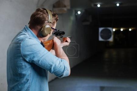 Photo pour Frapper l'œil des taureaux. bel homme sérieux confiant tenant le fusil et regardant dans la cible tout en essayant de frapper l'œil des taureaux - image libre de droit