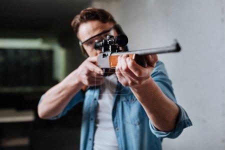 Photo pour Mon passe-temps. Agréable homme confiant visitant une galerie de tir et visant avec un pistolet tout en développant ses compétences - image libre de droit