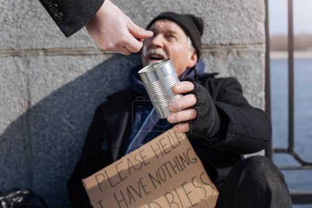 Glad gray-haired man keeping can for donation