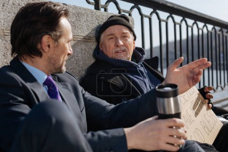 Profile photo of office worker while speaking with old man