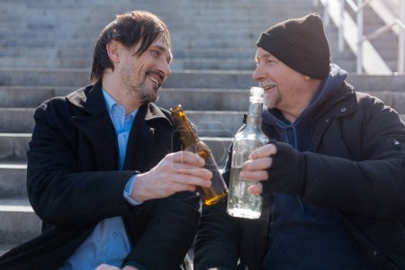 Positive delighted friends touching their bottles