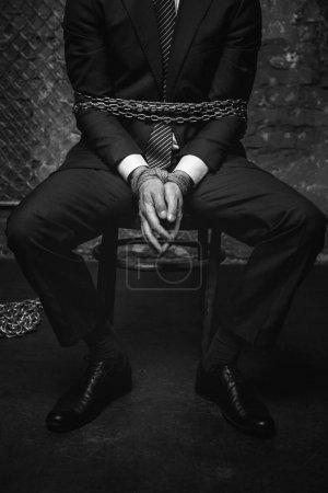 Broken helpless man tied with chains