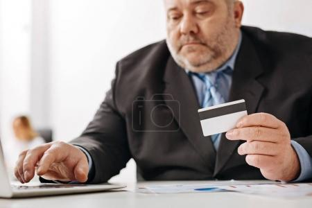 Concerned chubby guy checking his bank account