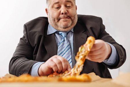 Unhealthy worker having some junk food for lunch