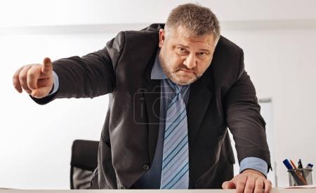 Powerful corpulent businessman threatening someone