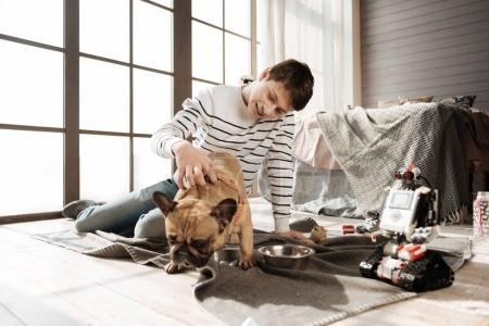 Positive delighted teenager putting right hand on the back of his dog