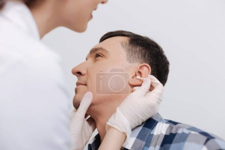 doctor looking into ear of her patient