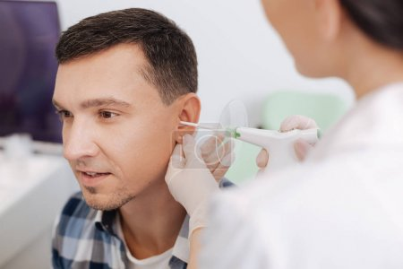 otolaryngologist holding ENT instrument