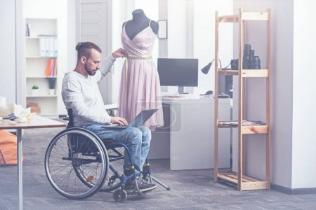 designer sitting on wheelchair in studio
