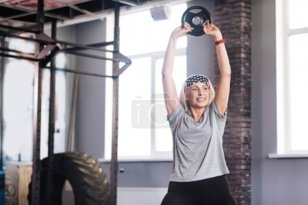 Delighted active woman lifting weights