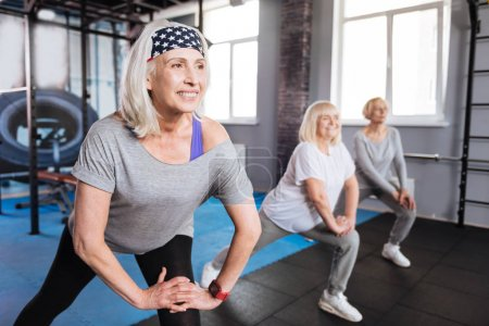 Photo for Being active. Cheerful sporty aged women smiling and doing physical exercises while visiting aerobic classes - Royalty Free Image