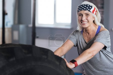 Delighted positive woman enjoying physical exercises
