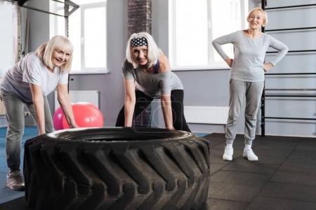Photo pour Nous sommes forts. Ravis de femmes séropositives sportives debout près d'un énorme pneu et en essayant de soulever tout en développant leurs muscles - image libre de droit