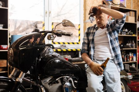 Delighted skillful mechanic tired after long a day
