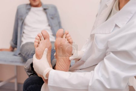 Trained competent specialist checking patients soles