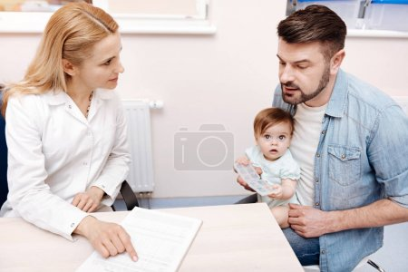 Attentive father sitting opposite family doctor